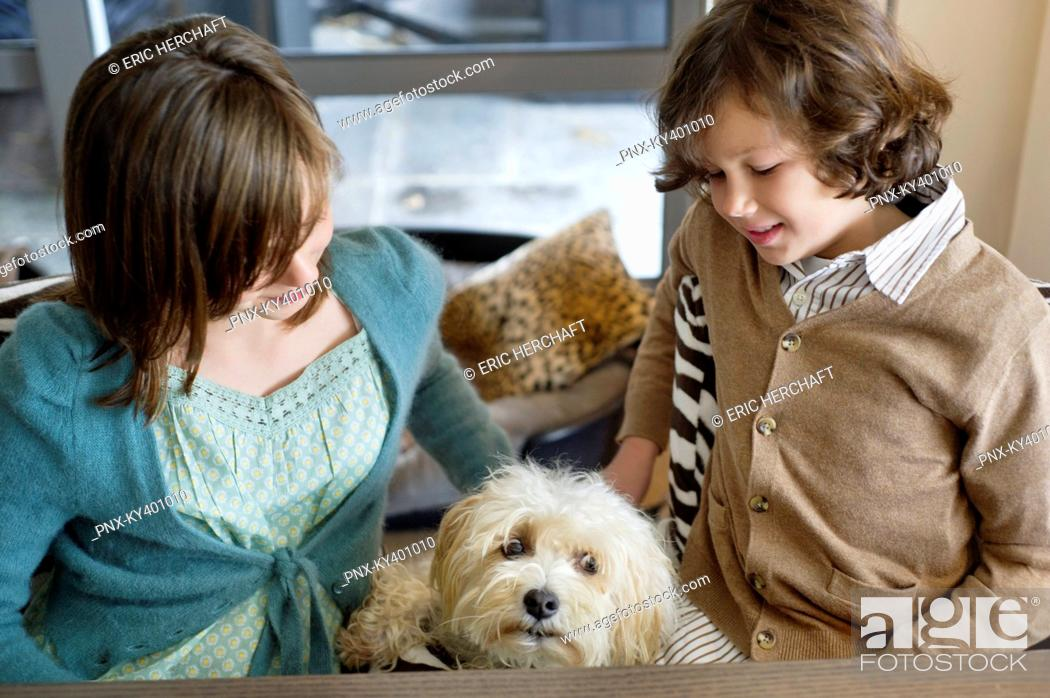 Stock Photo: Boy and his sister playing with a dog.