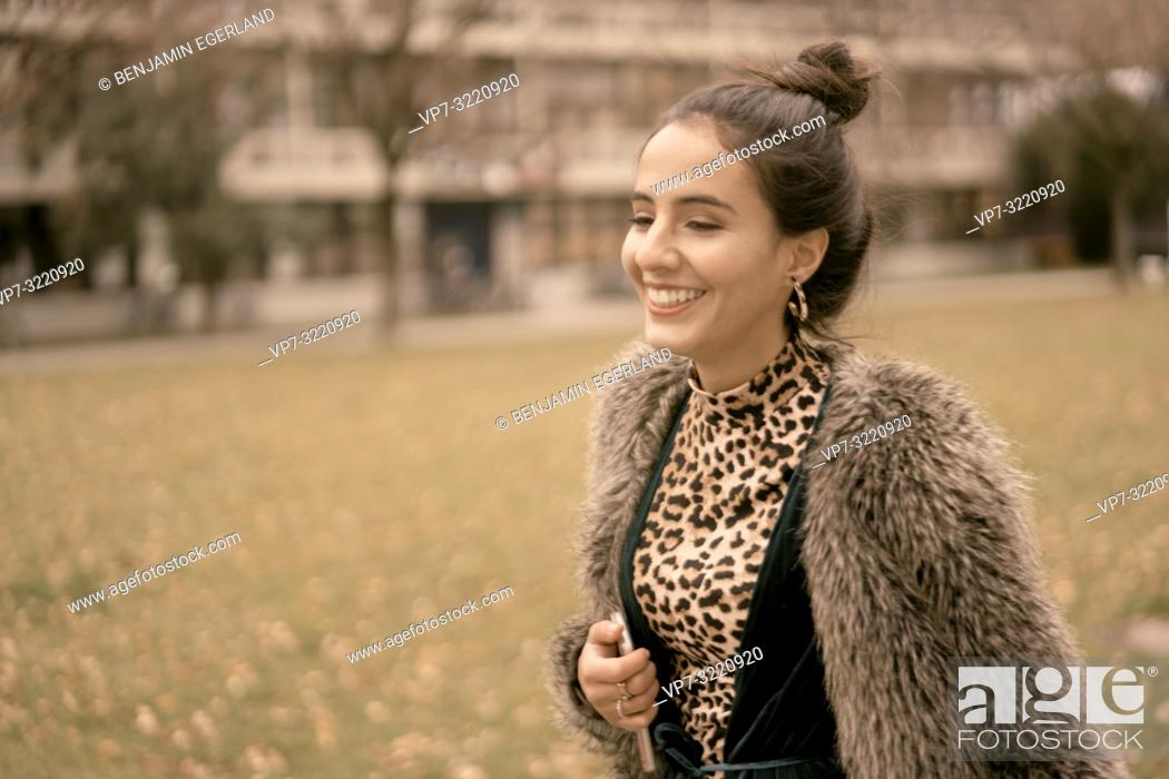 Stock Photo: fashionable vibrant woman running outdoors in park, closed eyes, autumn season, wearing coat, happy laughing, candid emotion, walking in city, Munich, Germany.
