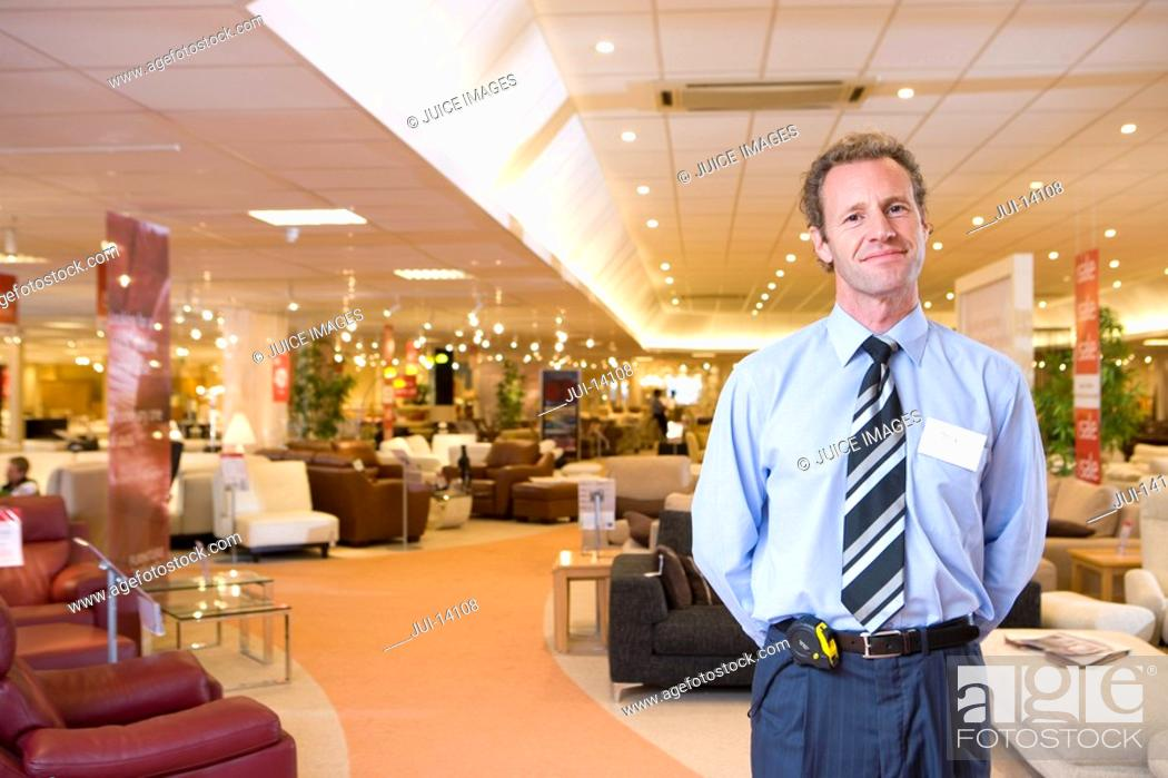 Stock Photo: Salesman in furniture shop, smiling, portrait.