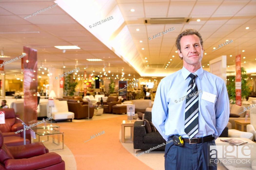 Stock Photo: Salesman in furniture shop, smiling, portrait.