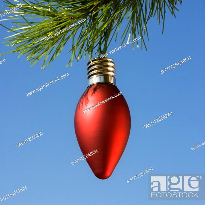 Stock Photo: Red ornament hanging on Christmas tree branch against blue background.