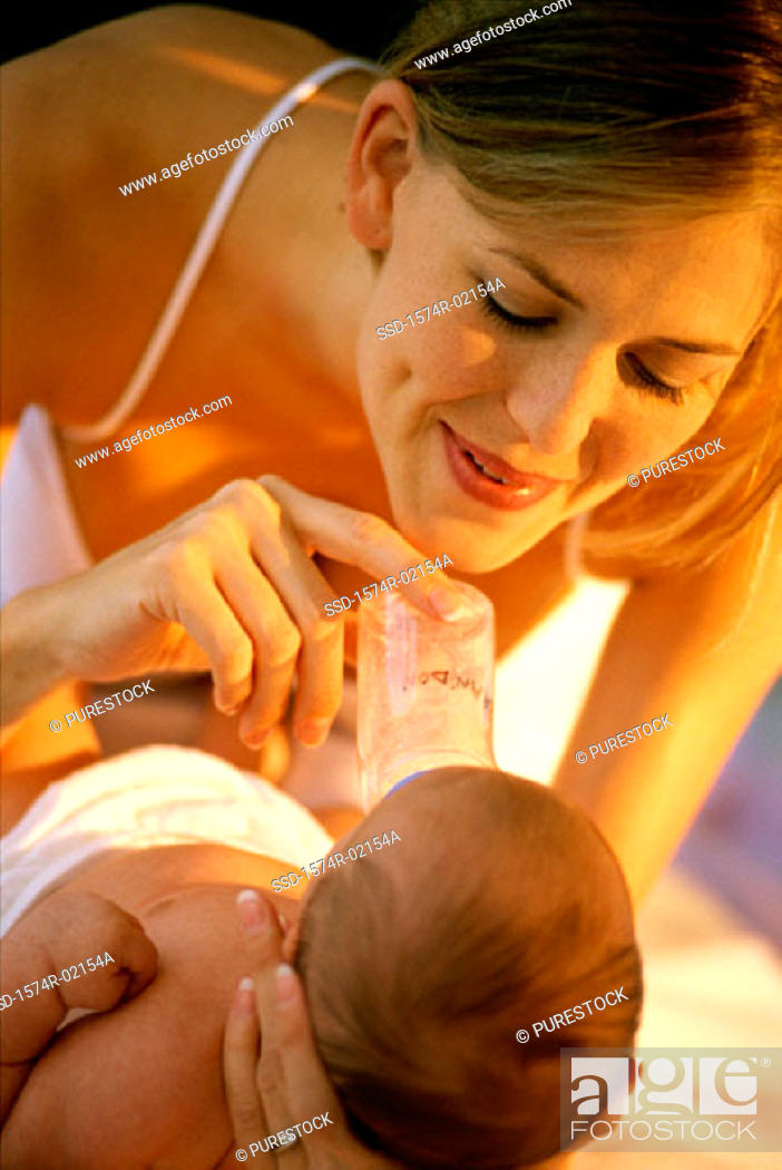 Stock Photo: Close-up of a mother feeding her baby girl with a baby bottle.