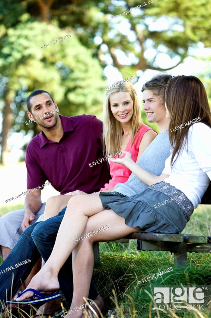 Stock Photo: Four young people sitting on a bench, talking.