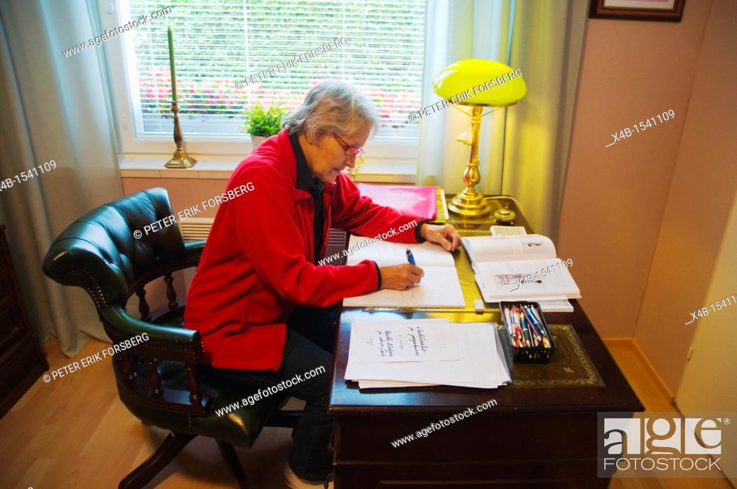 Stock Photo: Woman in her early 70s doing paperwork Finland Europe.