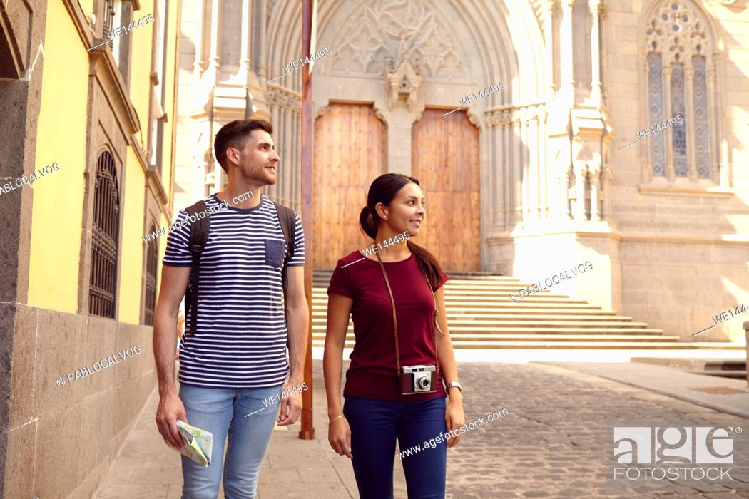 Stock Photo: Young tourist couple on vacation with a backpack and map looking sideways while walking dressed casually in jeans and t-shirts with a cathedral behind them.