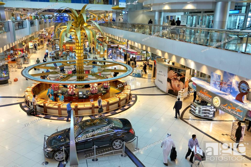 Stock Photo: Elevated view of the luxurious duty-free shop at Dubai International Airport with a stall selling golden jewelry by weight in the center. Dubai, UAE.
