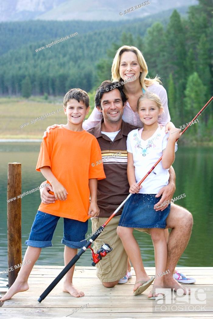 Stock Photo: Family of four with fishing rod on jetty, smiling, portrait.