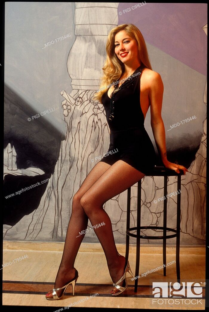 Moana pozzi posing with a short black dress and fishnets against the painted backdrop stock - Diva futura roma ...