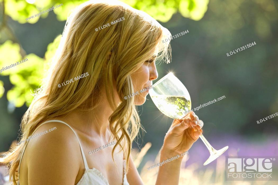 Stock Photo: A young woman drinking a glass of white wine.