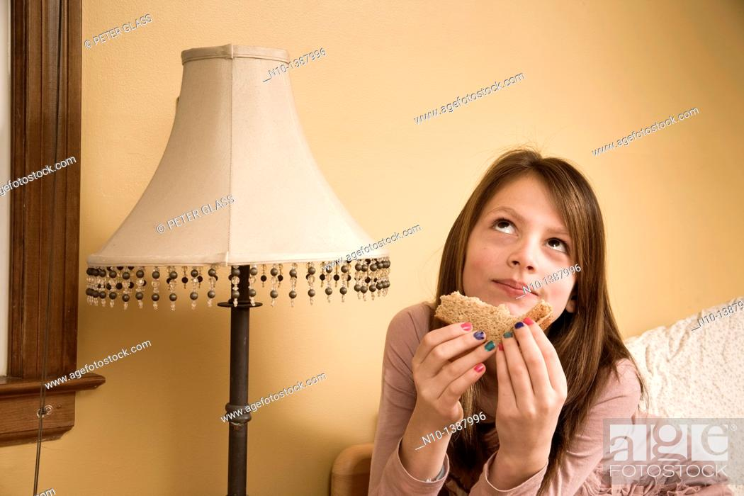 Stock Photo: Preteen girl eating a sandwich in her bedroom.