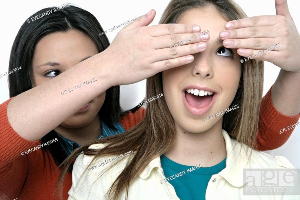 Stock Photo: Teenage girl covering hands over other girl's eyes.