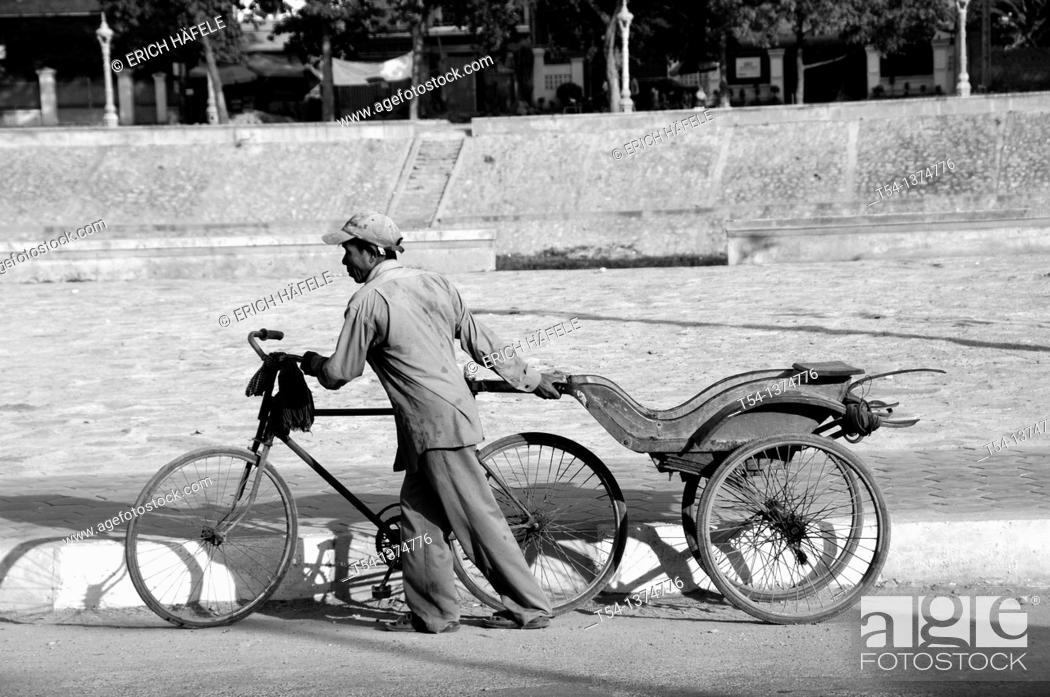 Stock Photo: Old Cambodian man pushes bicycle rickshaw.