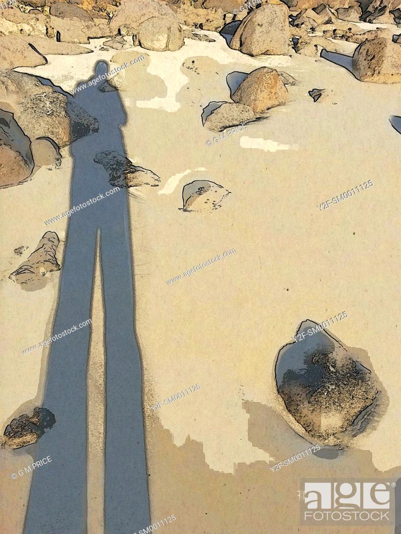 Stock Photo: long shadow of man on rocky beach.