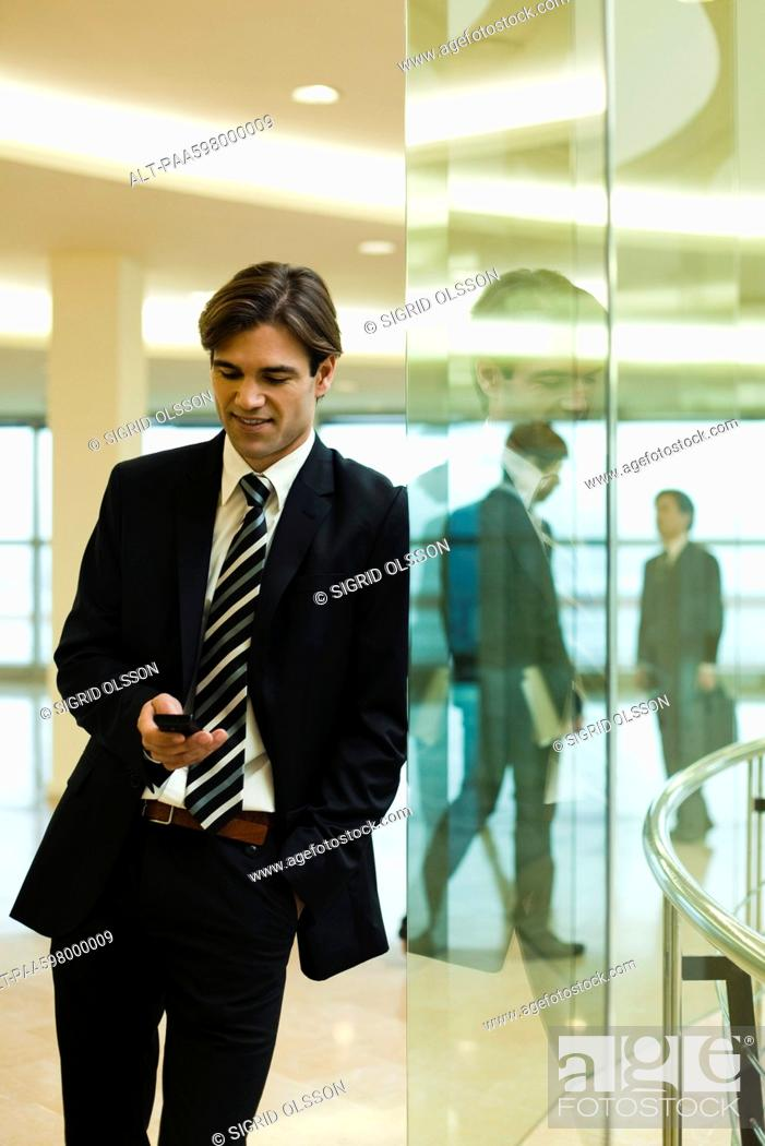 Stock Photo: Businessman text messaging in lobby.