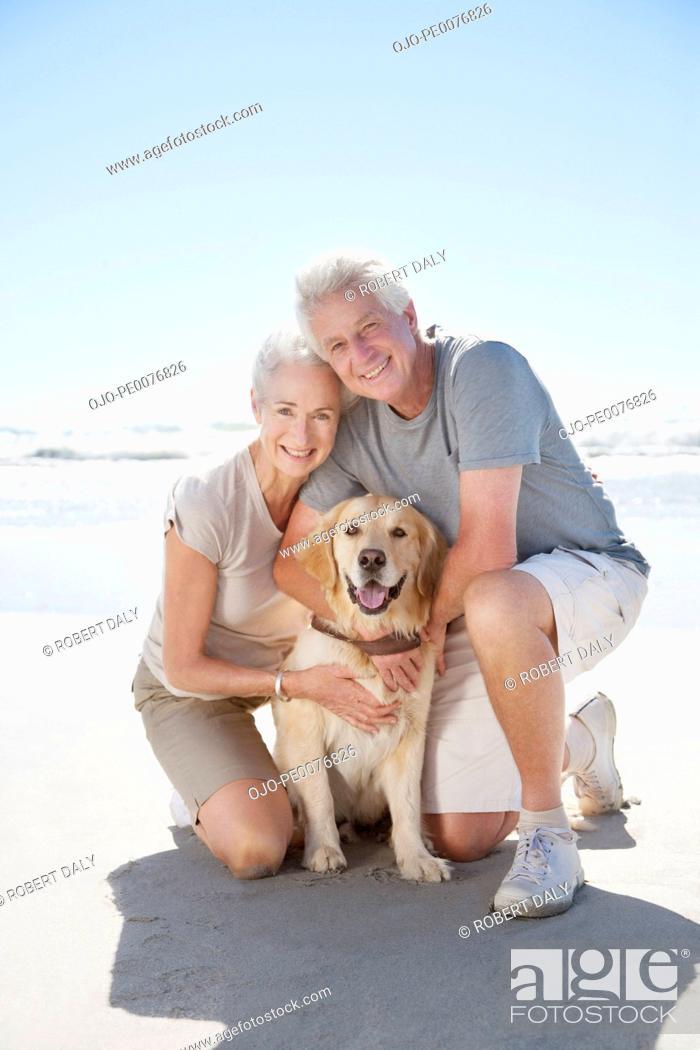Stock Photo: Senior couple with dog on beach.
