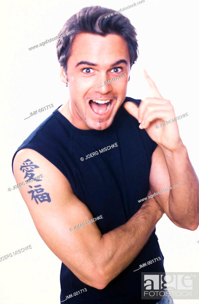 Stock Photo: Portrait of a young man, 20-25 25-30 30-35 dark-haired, masculine, powerful, strong, athletic and beautiful in a black sleeveless tee-shirt.