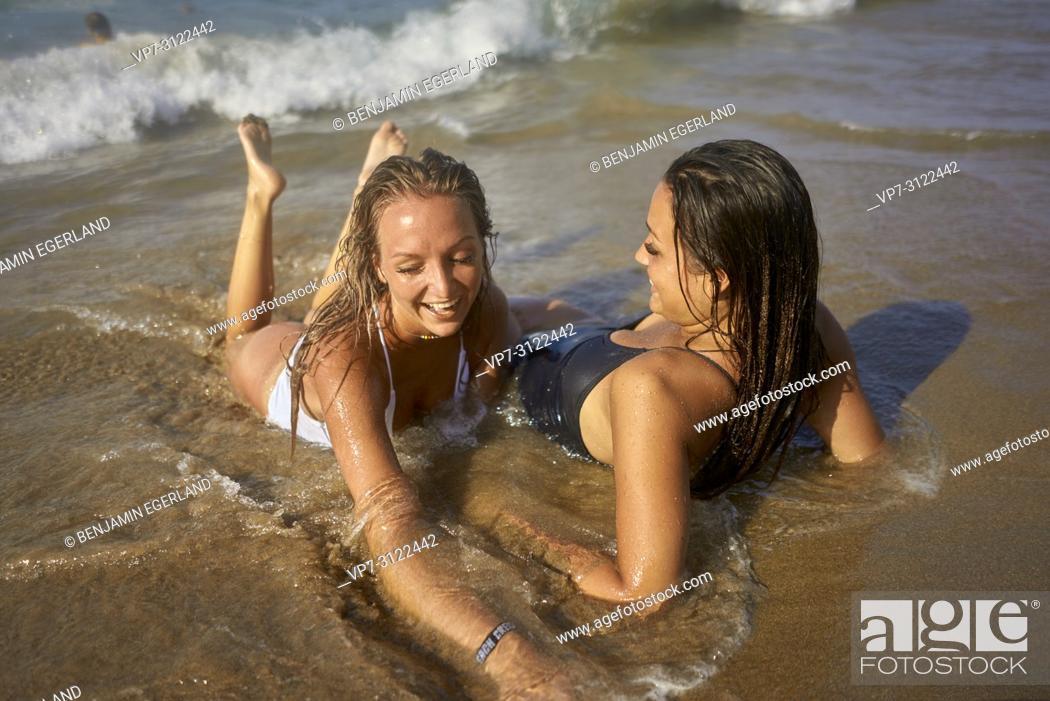 Imagen: Two young women relaxing on beach. Chersonissos, Crete, Greece.