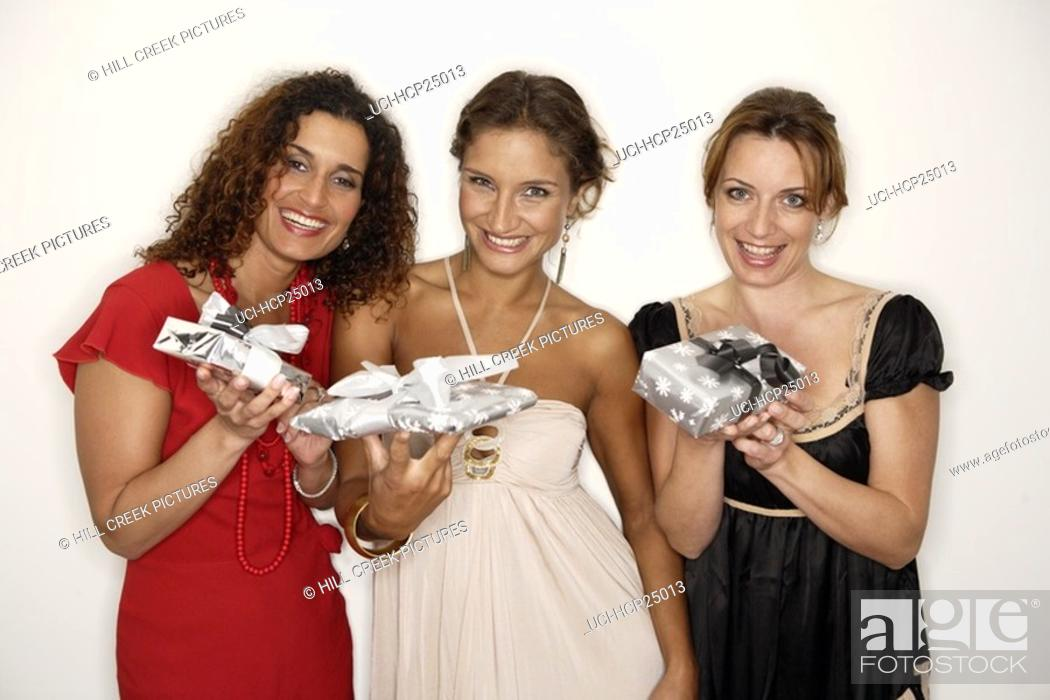 Stock Photo: Women holding Christmas gifts.