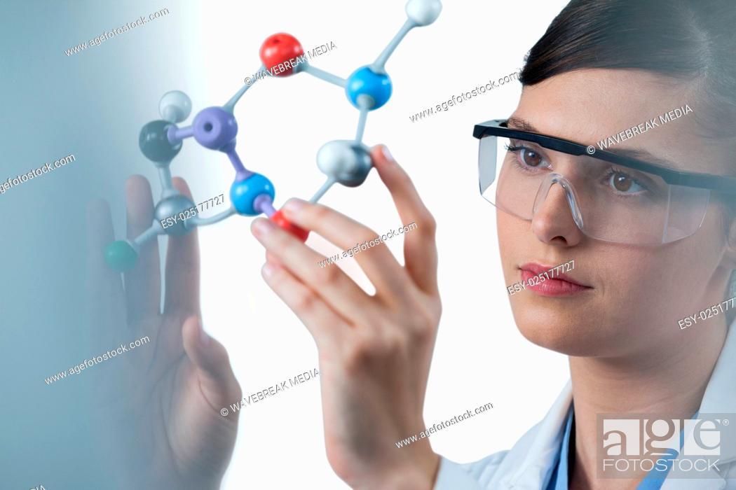 Stock Photo: Female scientist holding molecular model.