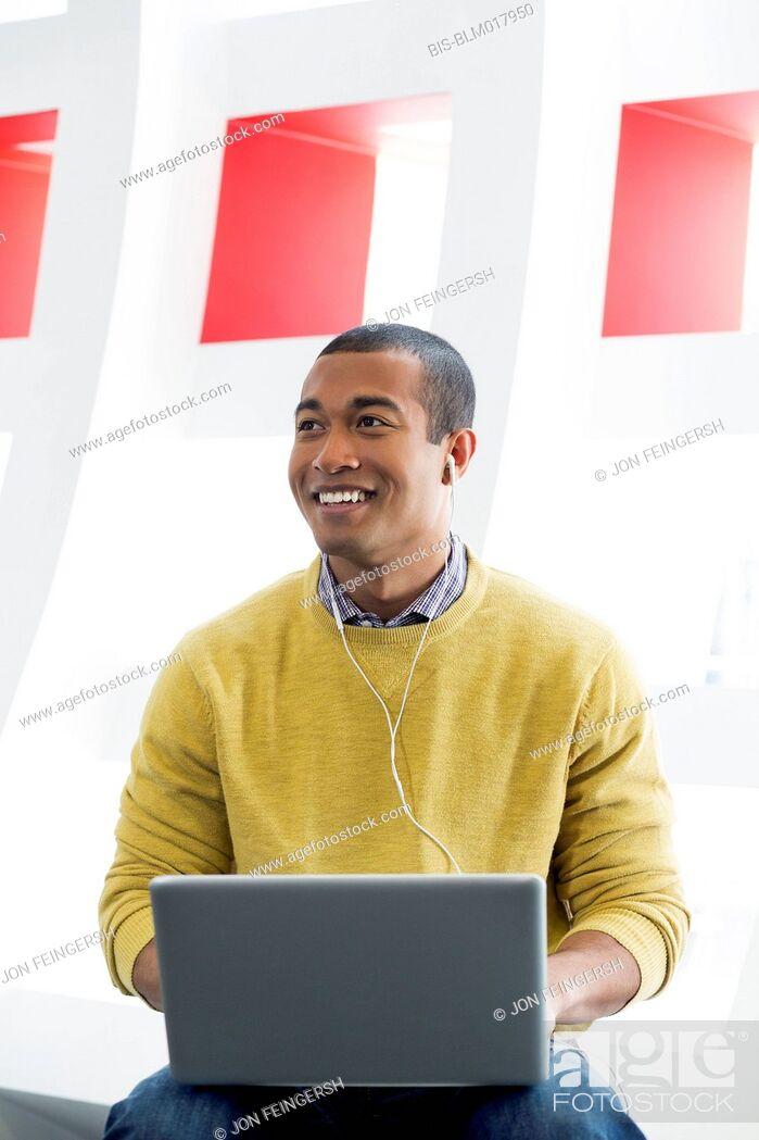 Imagen: Mixed race man using laptop and earphones.