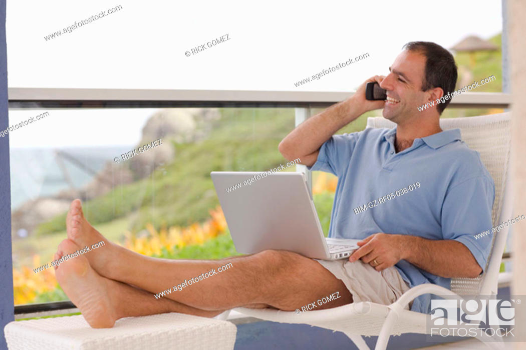 Stock Photo: Man sitting on balcony with cell phone and laptop, Florianopolis, Brazil.