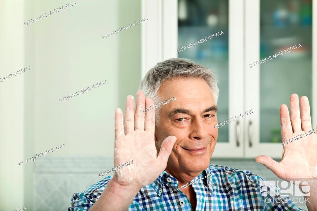 Stock Photo: Germany, Berlin, Senior man showing handful of flour, portrait.