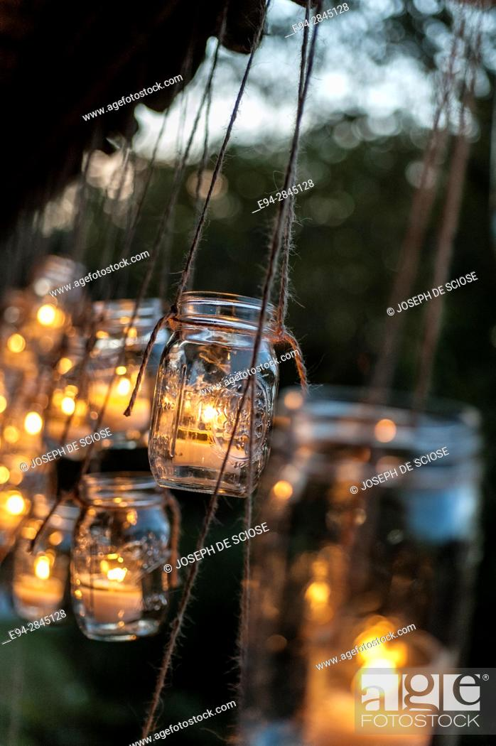 Stock Photo: Hanging Mason jars holding lighted candles outdoors.