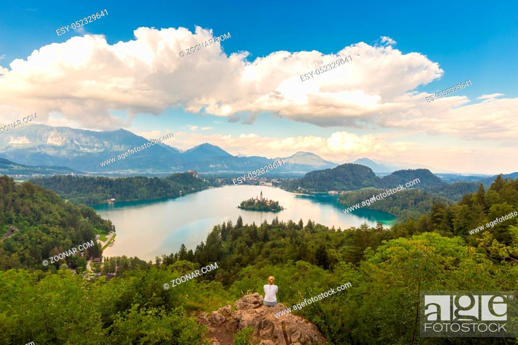 Stock Photo: Relaxed female traveler enjoying beautiful panoramic view of Julian Alps, Lake Bled with St. Marys Church of the Assumption on the small island, Bled, Slovenia.