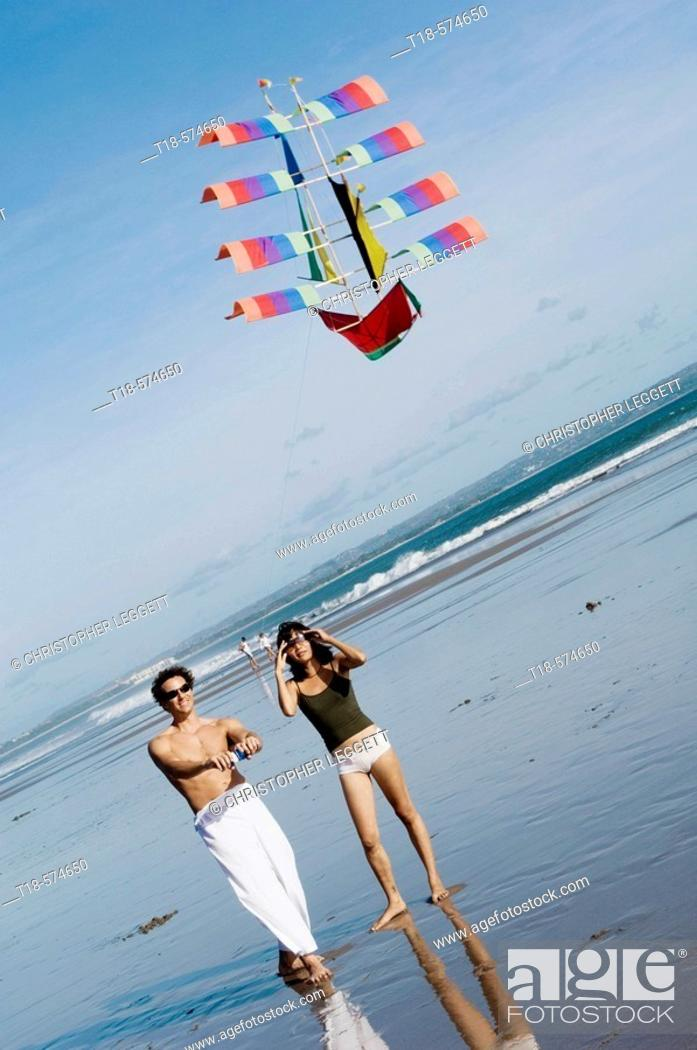 Photo de stock: couple playing kite on beach.