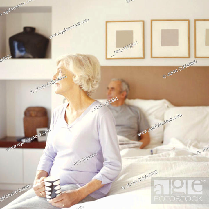 Stock Photo: Senior couple in bedroom, woman sitting on end of bed holding cup.