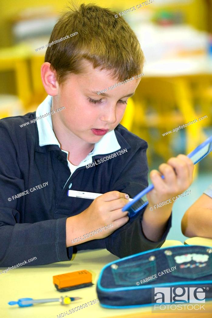 Stock Photo: Young boy writing on a plastic slate in a classroom.