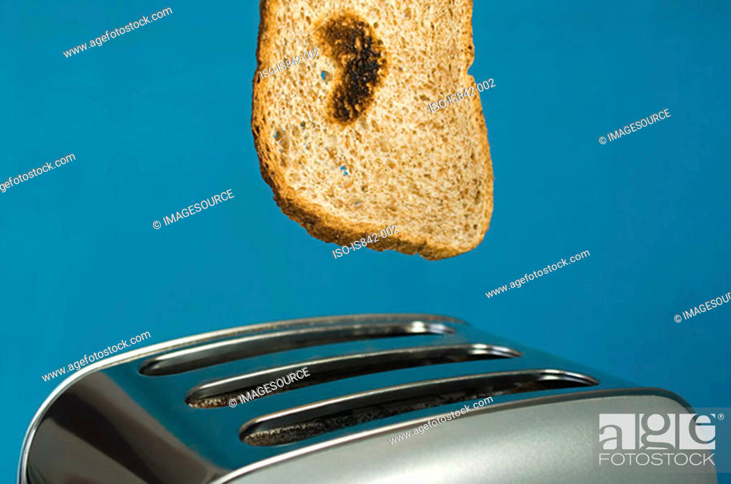 Stock Photo: Toast with heart shape burn and toaster.