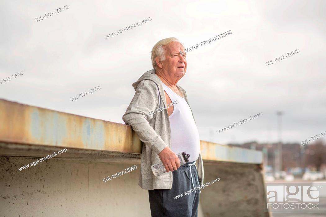 Stock Photo: Man wearing sports clothes holding water bottle looking away.