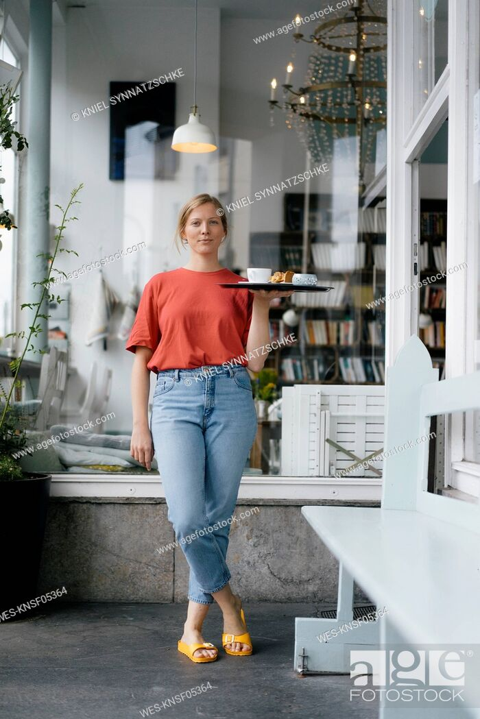 Stock Photo: Portrait of young woman serving coffee and cake in a cafe.