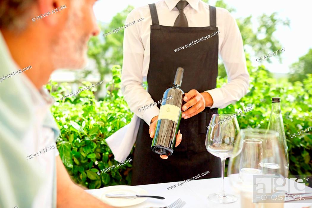 Stock Photo: Wine steward showing wine bottle to man dining on patio.
