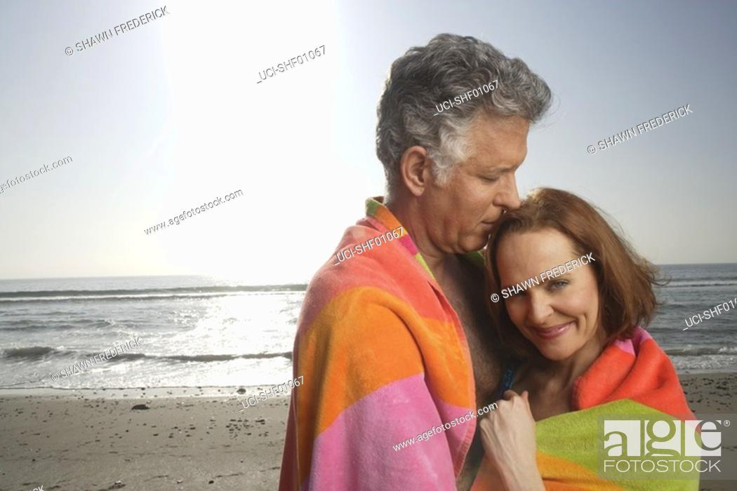 Imagen: Mature couple kissing on the beach.