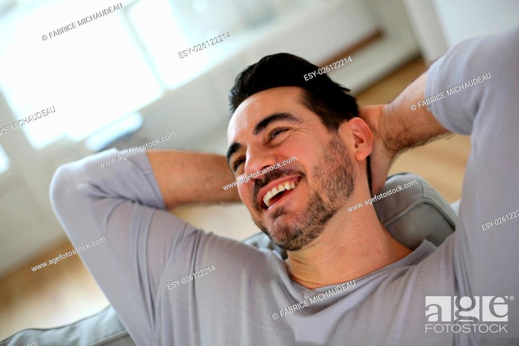 Photo de stock: Relaxed man stretching arms behind head.