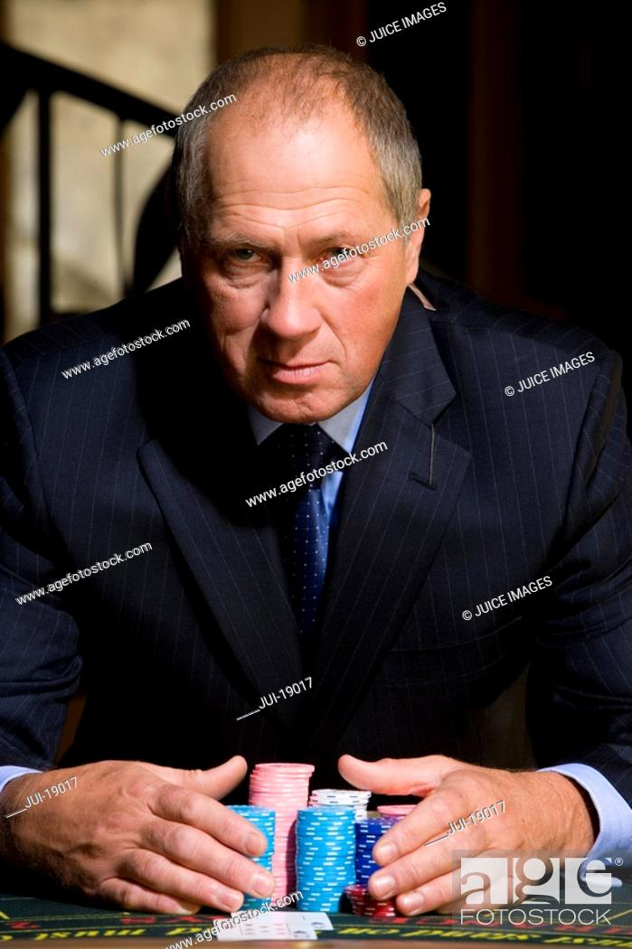 Stock Photo: Mature man at poker table, hands on gambling chips, portrait.
