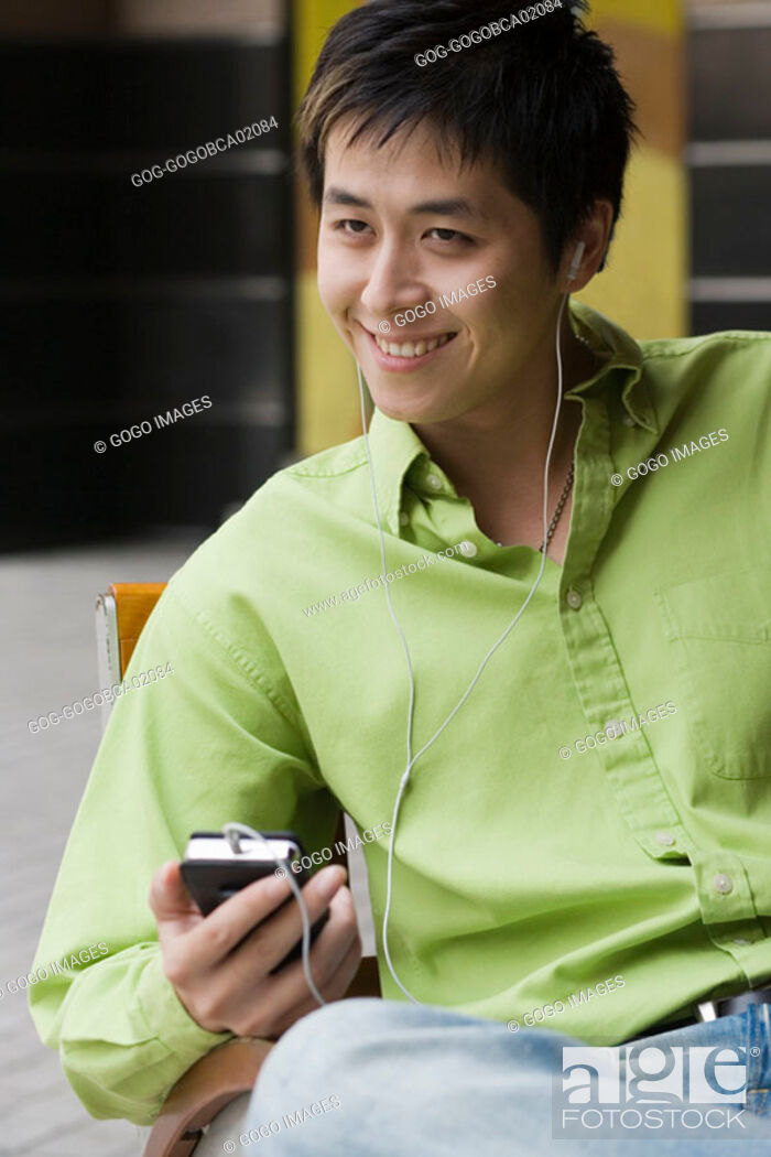 Stock Photo: Young man listening to his mp3 player.