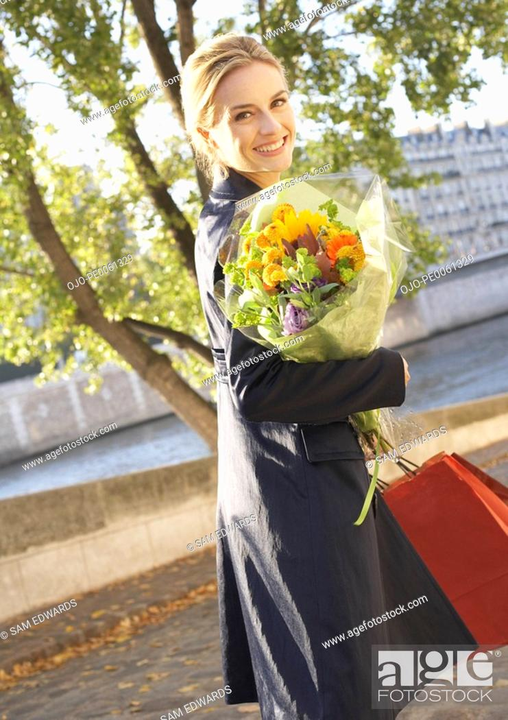 Stock Photo: Woman outdoors with shopping bags and flowers smiling.