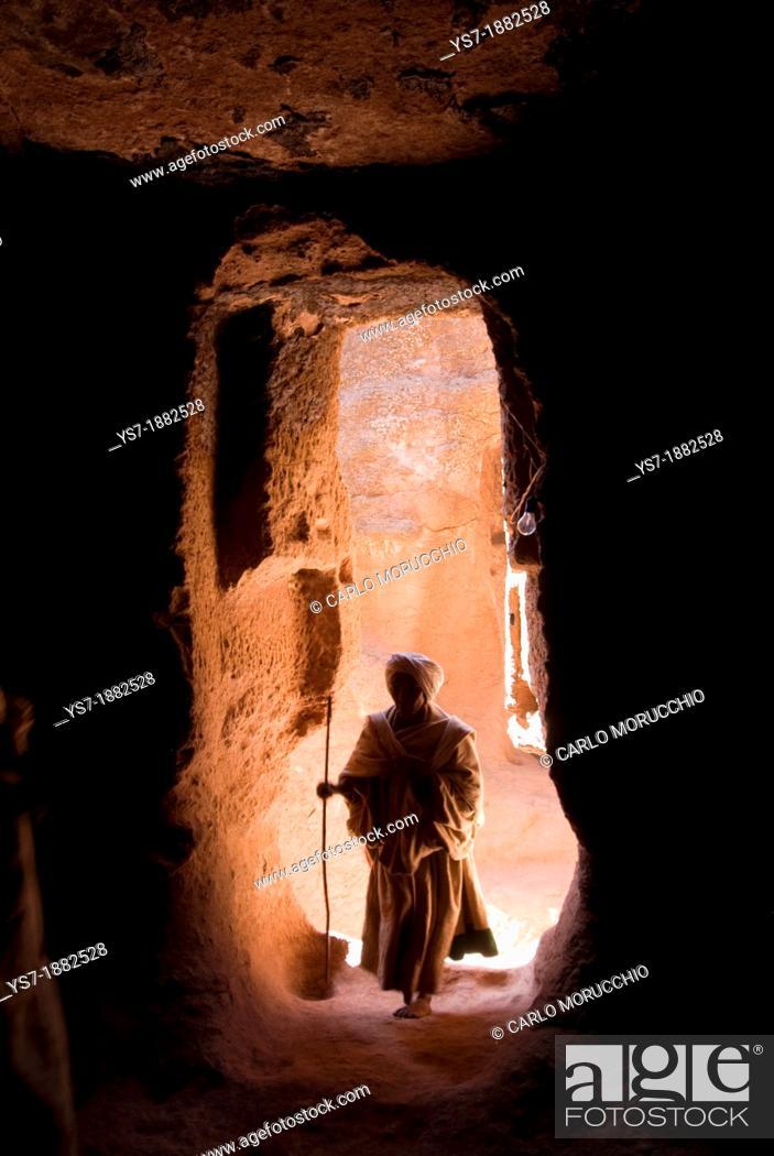 Stock Photo: Pilgrim walking through a narrow passage to reach the entrance of Bet Amanuel monolithic rock-cut church in Lalibela, Ethiopia, Africa.