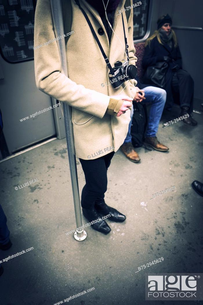 Stock Photo: Man standing inside subway car with old analog camera. Berlin, Germany.