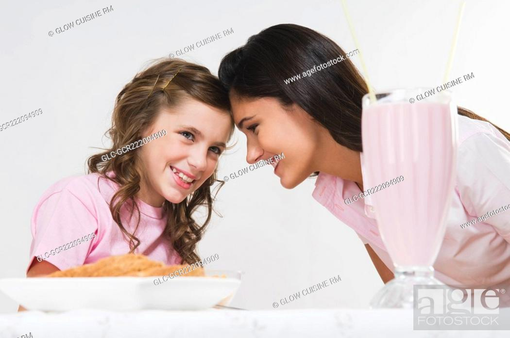 Stock Photo: Woman with her daughter at a breakfast table.