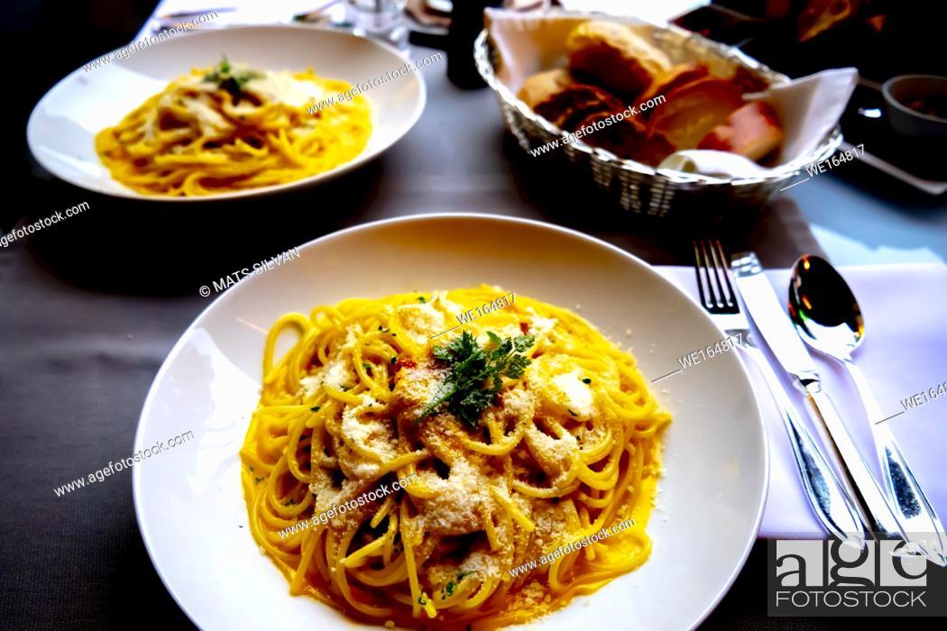 Stock Photo: Carbonara Spaghetti and Bread on Table in Milan, Italy.