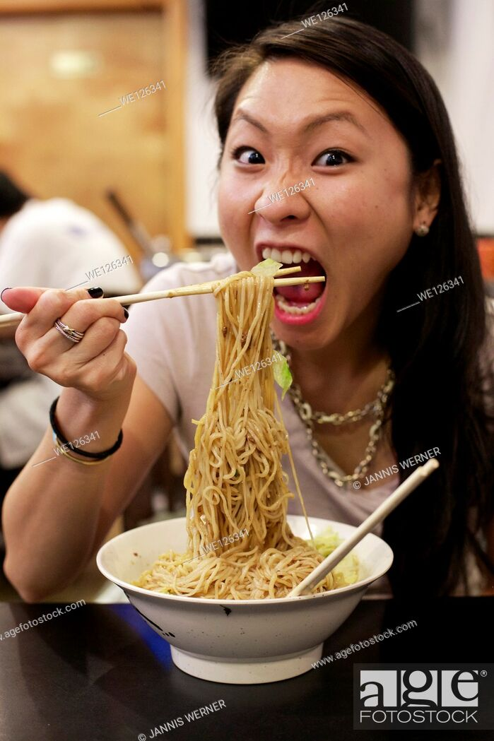Stock Photo: Young Asian girl eating Chinese noodle dish at a restaurant in Chinatown Manhattan, New York, NY, USA.