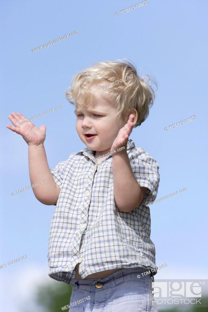 Stock Photo: Germany, Bavaria, Boy clapping hands, close up.