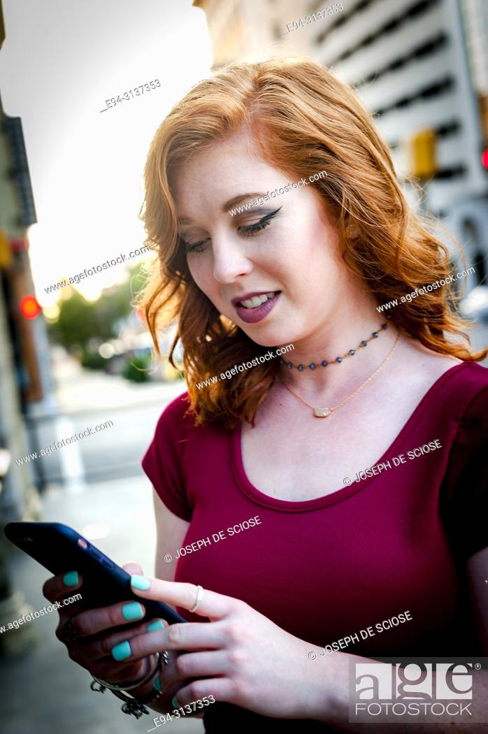 Stock Photo: A pretty 25 year old redhead woman standing on a city street looking at her mobile phone.