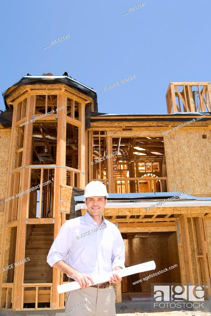 Stock Photo: Architect with blueprint in front of partially built house, smiling, portrait, low angle view.