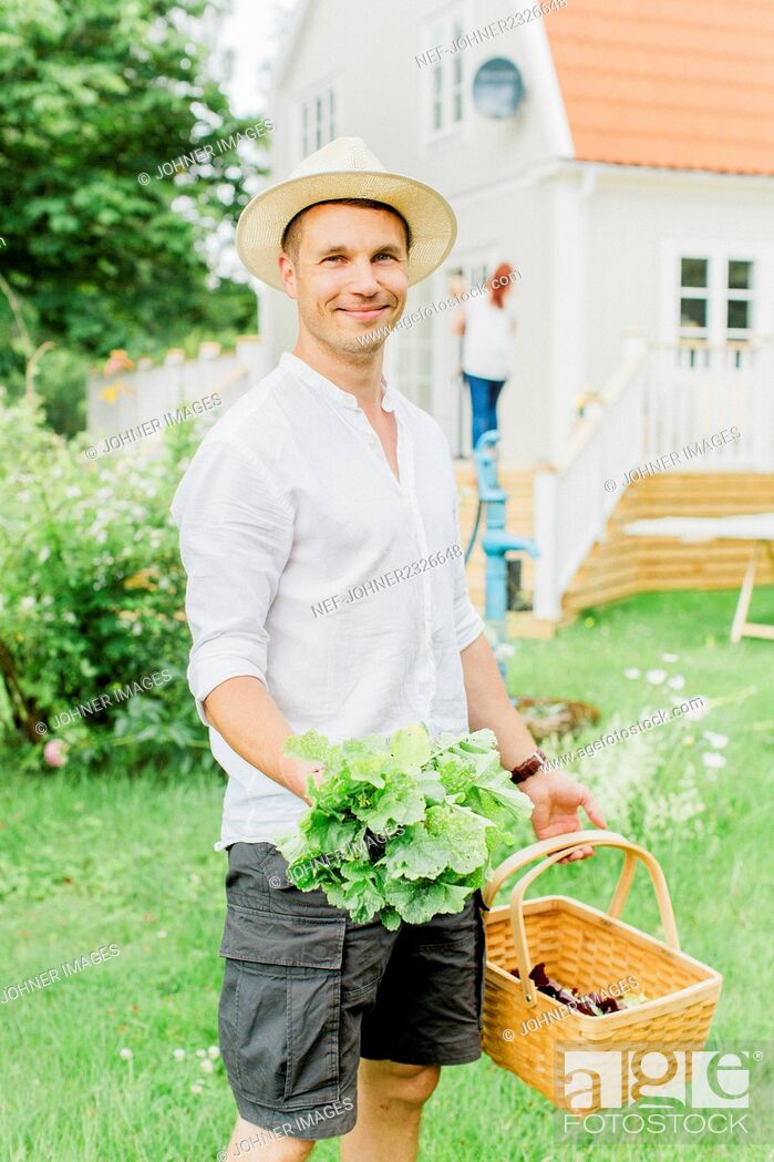 Stock Photo: Man with basket and fresh vegetables in garden.