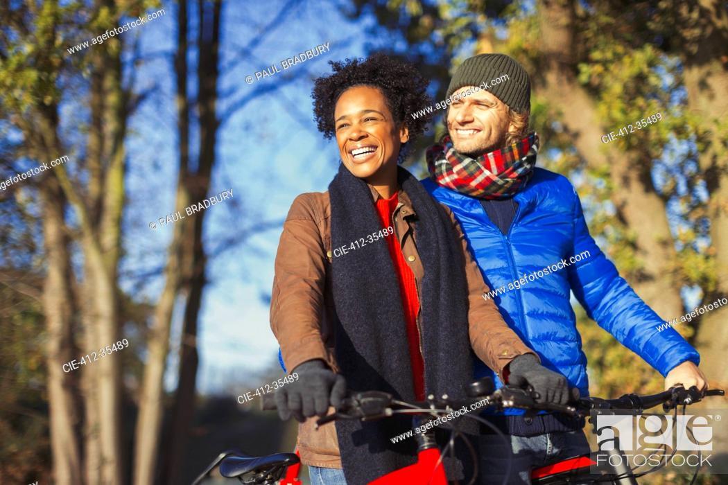 Stock Photo: Smiling couple bike riding in sunny autumn park.